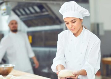 Apprentice baker shaping a loaf of bread at a bakery