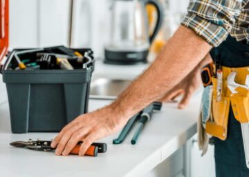 A plumber setting out tools on a kitchen bench
