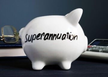 A white piggy bank on a desk representing superannuation savings