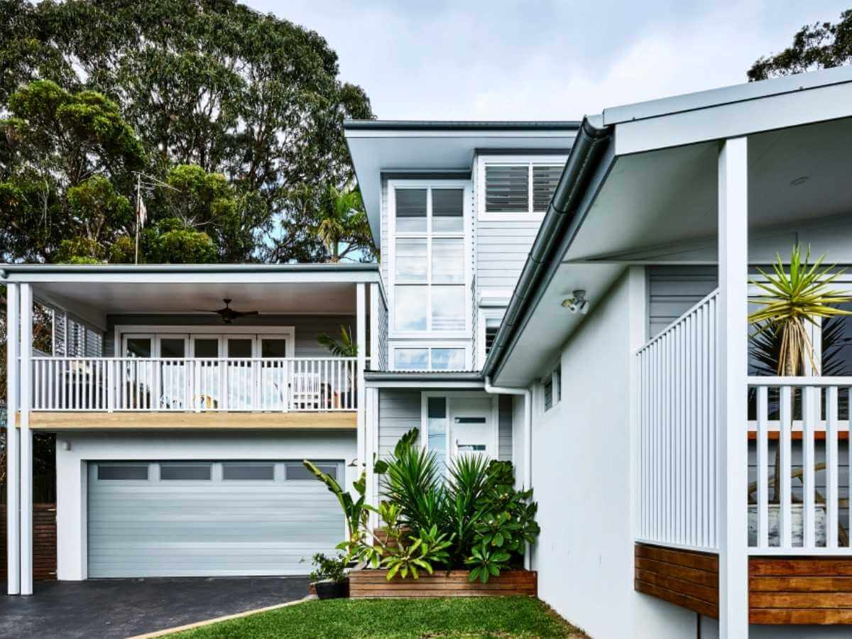 A grey coastal style home with a granny flat bungalow off to the side