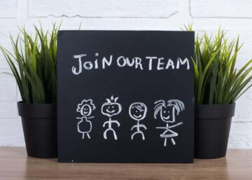 Join our team text written on a small blackboard propped up against potted plants