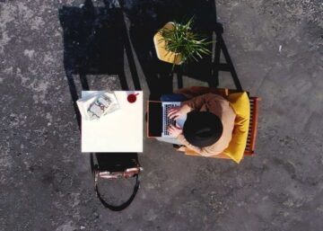 Top down view of a man in an orange shirt working from home on a laptop