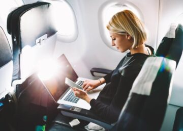Young business woman checking phone and laptop during a plane flight