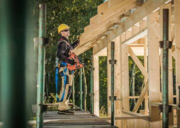 Image of a builder with a nail gun working on a house construction