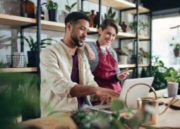 Shop assistants with laptop working in a potted plant store