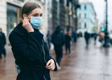 Portrait of a young woman wearing a mask in a city street.
