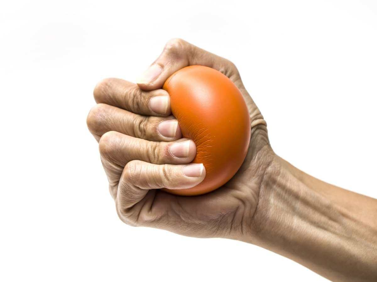 A woman's hand squeezes an orange stress ball on a white background