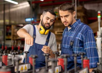 Young trainee looking at industrial equipment while listening to manager