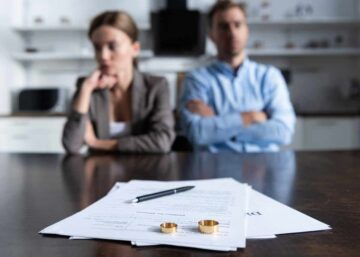 A separated couple sit at a table to sign divorce papers