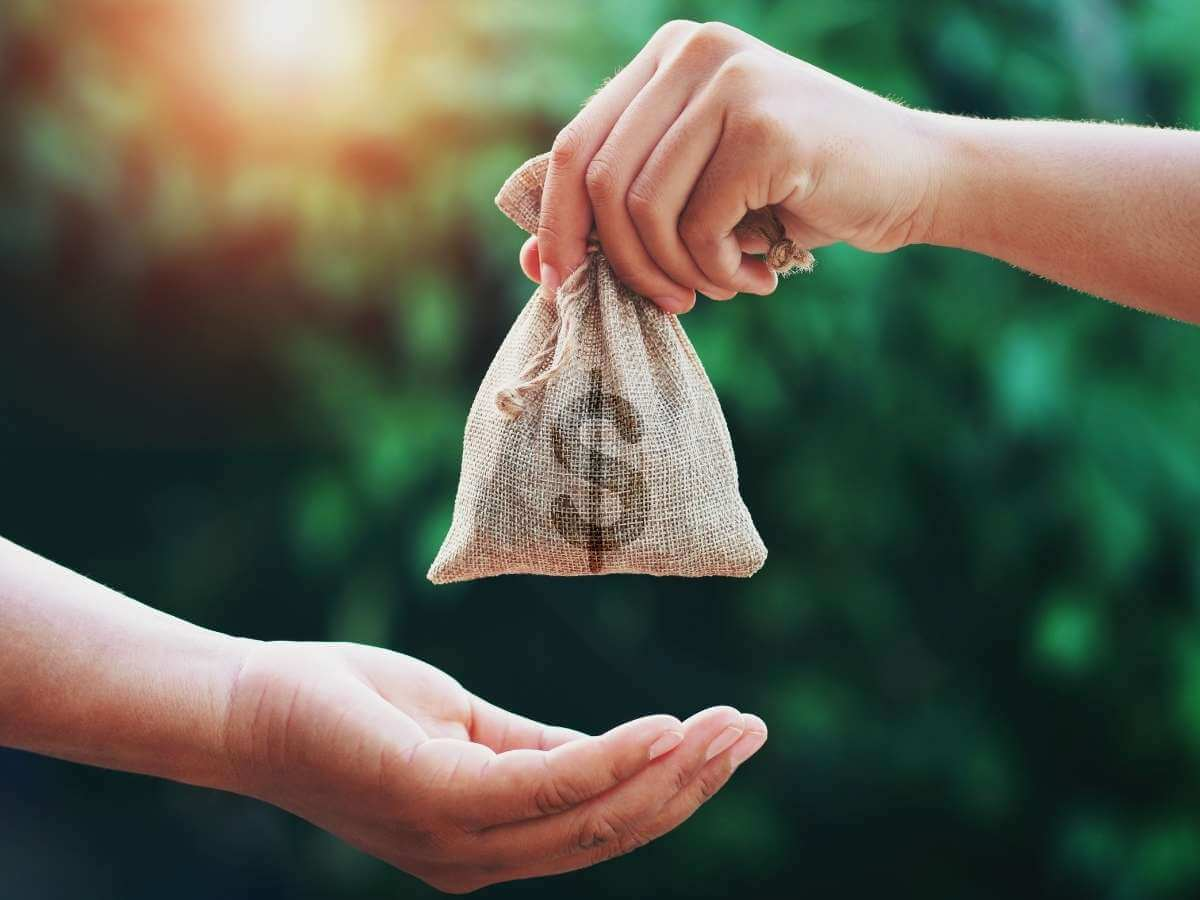 A bag of money is handed to from one person to another with greenery in the background