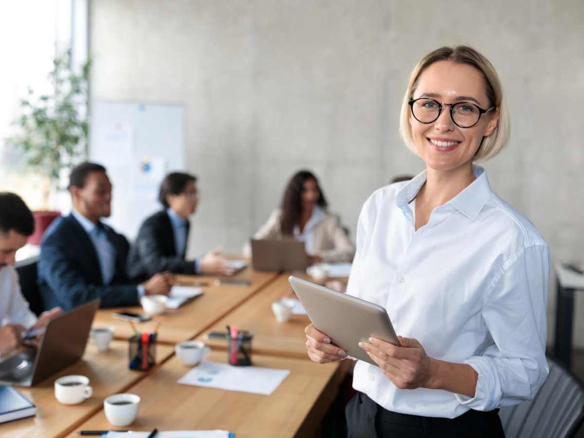 Coworkers meet around a boardroom table in a modern office.