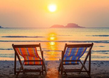 A pair of beach loungers on the deserted beach at sunset.